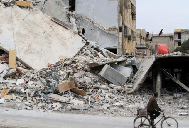 A man rides a bicycle past a damaged building in Daraya, near Damascus February 2, 2014. Picture taken February 2, 2014.REUTERS/Omar Abu Bakr/Files