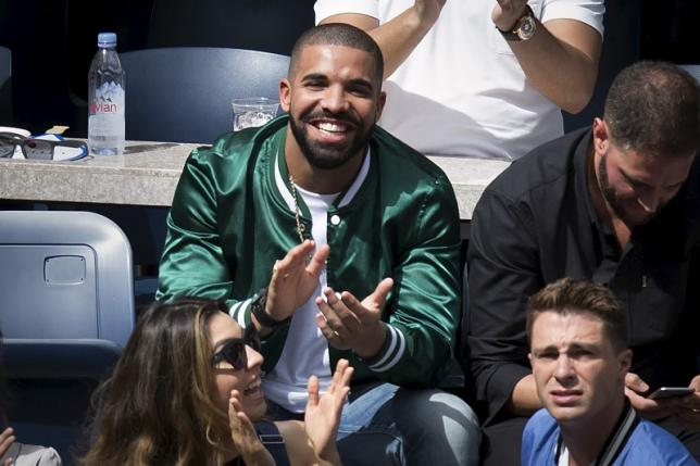 Musician Drake applauds as his image is displayed on the TV monitors during the Serena Williams, Roberta Vinci match at the U.S. Open Championships tennis tournament in New York, September 11, 2015. Picture taken September 11, 2015.  REUTERS/Carlo Allegri
