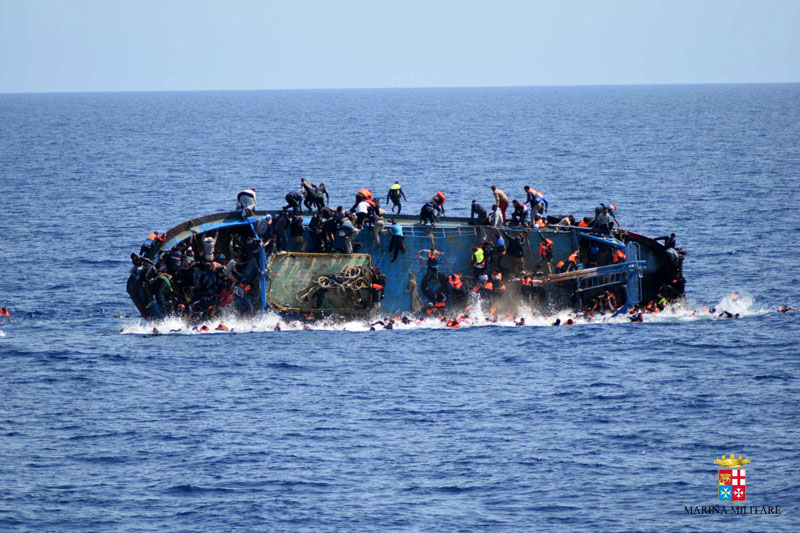 People jump off a boat moments before it overturns off the Libyan coast, on Wednesday, May 25, 2016. Photo: Marina Militare via AP