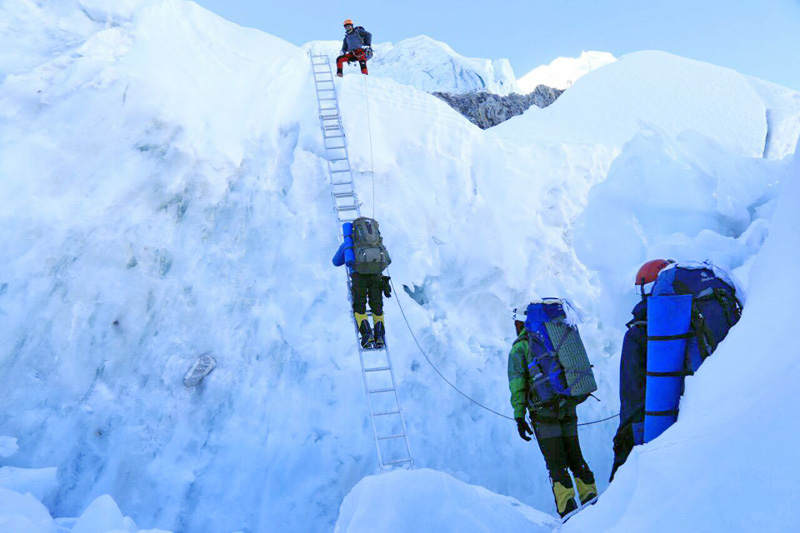 Climbers try to walk past the ladder while ascending to Mt Everest, on Monday, May 9, 2016.