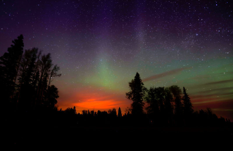 The wildfires glow underneath The Northern Lights, also known as the Aurora Borealis, near Fort McMurray, Alberta, Canada, on May 7, 2016. Photo: Mark Blinch/Reuters