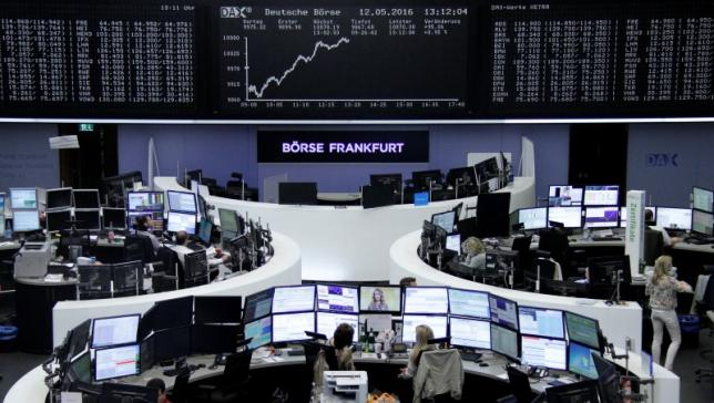 Traders work at their desks in front of the German share price index, DAX board, at the stock exchange in Frankfurt, Germany, May 12, 2016.     REUTERS/Staff/Remote