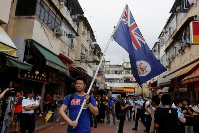 A local protester against mainland Chinese parallel traders carries a British Hong Kong colonial flag in Hong Kong, China, May 1, 2016. REUTERS/Bobby Yip