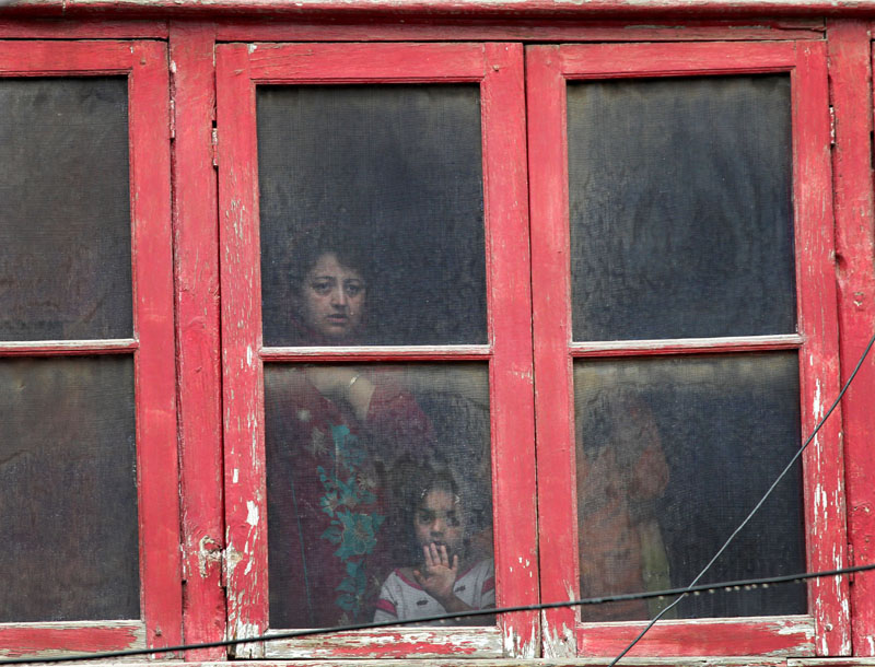 A Kashmiri family watches from the window of their house near the site of a gunbattle in Srinagar, Indian controlled Kashmir, on Tuesday, May 24, 2016. Photo: AP