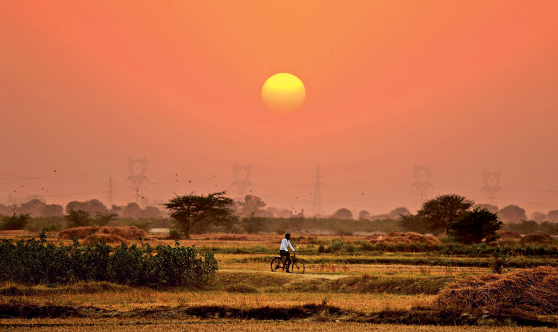 An Indian cyclist rides in front of the setting sun in the village of Anandpur in the northern state of Uttar Pradesh, soon after the village was electrified, on April 23, 2016. Photo: AFP
