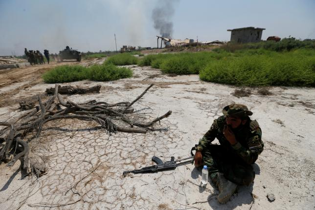 A fighter from Iraqi Shiite group Kataib Sayyid al-Shuhada takes a break at a site near the frontline of the fight against Islamic State militants near Falluja, Iraq, May 23, 2016. REUTERS/Thaier Al-Sudani