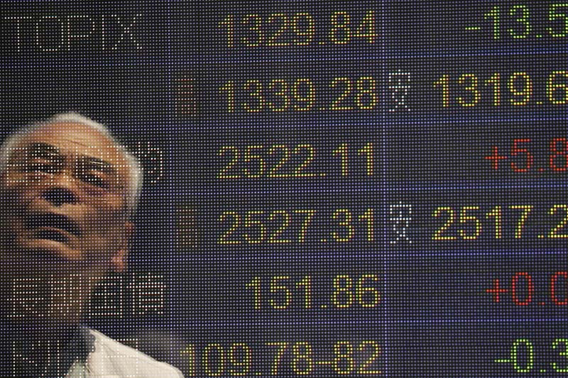 A man is reflected on the electronic board of a securities firm in Tokyo, on Monday, May 23. 2016. Photo: AP