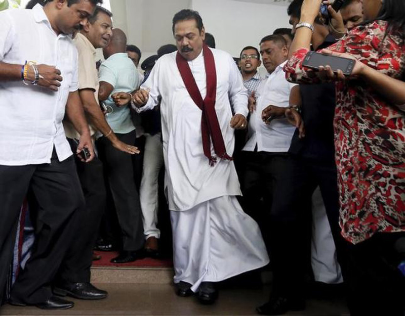 Sri Lanka's former president Mahinda Rajapaksa (C) reacts after taking a misstep as he left the Special Presidential Commission of Inquiry centre, in Colombo October 15, 2015. Photo: Reuters