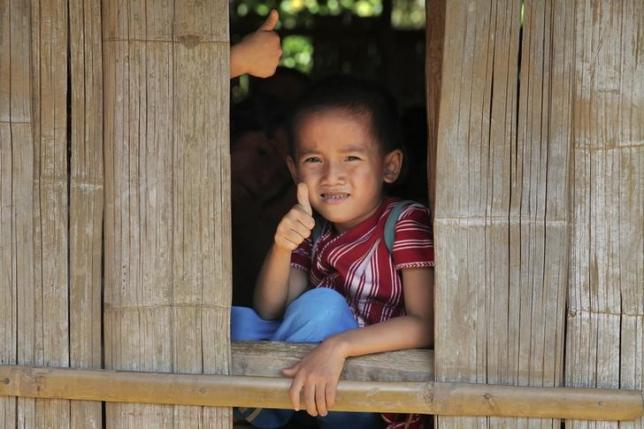 A primary school student at the Ei Thu Ta camp for displaced Karens along the Salween river in Myanmar gives a thumb-up November 17, 2014.  REUTERS/Thin Lei Win/Files
