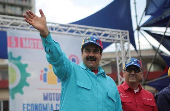 Venezuela's President Nicolas Maduro (C) greets supporters during a rally, next to Venezuela's Economy and Productivity Vice President Miguel Perez Abad, in Caracas, Venezuela May 14, 2016. Miraflores Palace/Handout