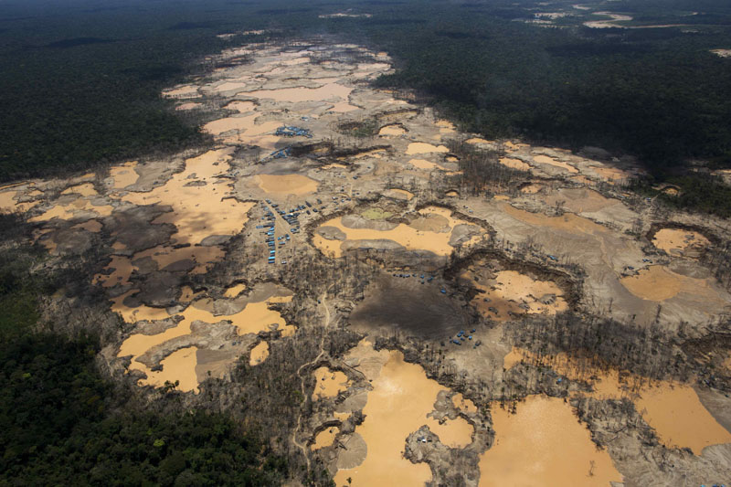 FILE -  A deforested area dotted with blue tarps, marking the area where miners reside, and craters filled with water, caused by illegal gold mining activities, in La Pampa, in Peru's Madre de Dios region, on November 11, 2014. Photo: AP