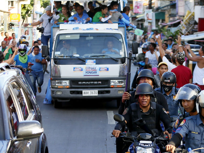SWAT members of the Philippine National Police provide security to the campaign motorcade of presidential candidate Vice-president Jejomar Binay and congressman Manny Pacquiao, who is running for senator in Monday's national elections during their campaign rally in Navotas north of Manila, Philippines, on Friday, May 6, 2016. Photo: Bullit Marquez/AP