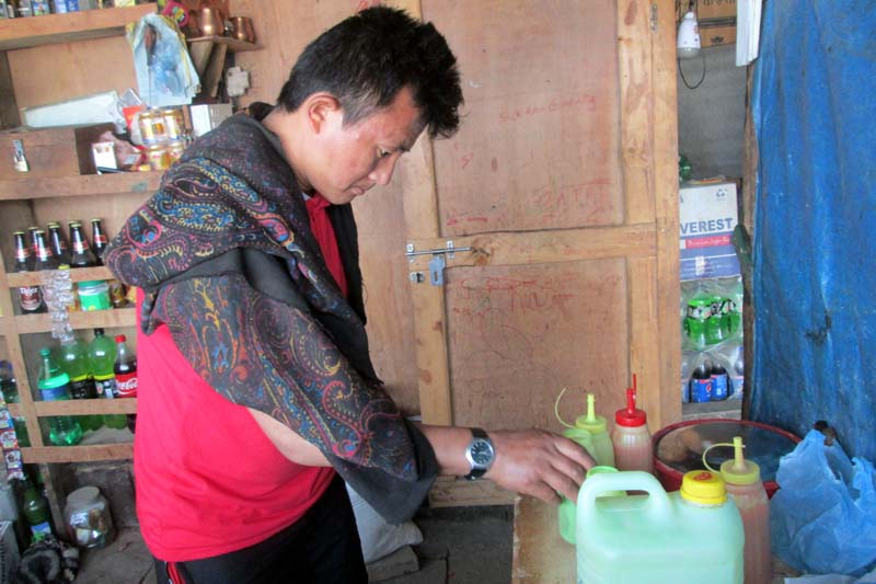 Sukaram Gurung, who had lost his hand in the April 25 earthquake last year, working at his tea shop in Barpak, Gorkha, on Saturday, April 30, 2016. Photo: THT