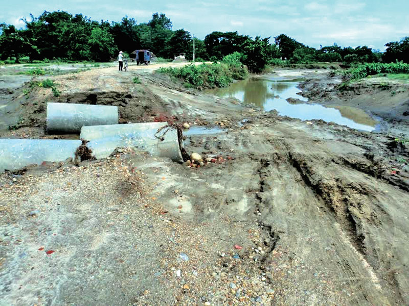 A tempo is seen crossing a damaged part of Rajbiraj-Kunauli road, on Saturday, May 21, 2016. Photo: THT