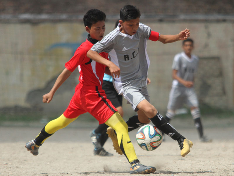 A player from Reliance Co-Ed (right) beats past his Tillingtar opponent during the Coca-Cola Cup Inter-school Football Tournament in Kathmandu on Thursday. Photo: Udipt Singh Chhetry/THT