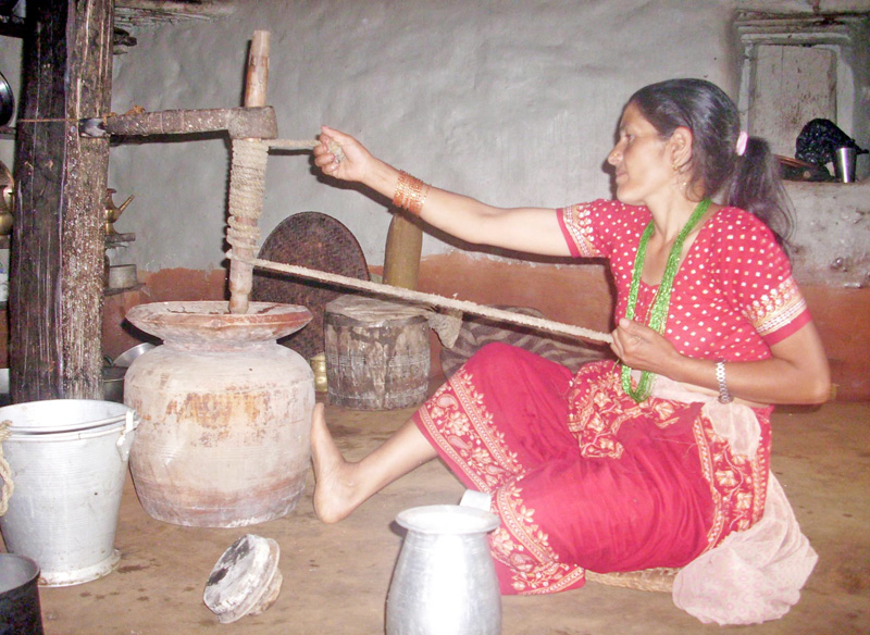 A woman uses tradition tools to skim <i>dahi</i> in Khotang district, on Monday, May 9, 2016. Photo: RSS