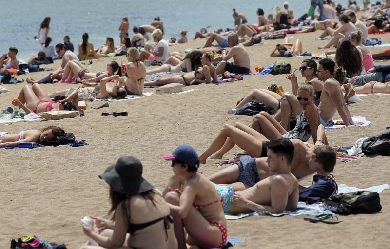 People sunbathe at the Barceloneta beach in Barcelona, Spain, on Wednesday, May 25, 2016. Photo: AP