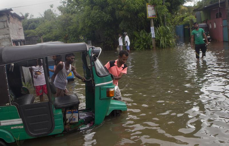 Sri Lankan men push an auto rickshaw stranded in a flooded road after heavy rains in Colombo, Sri Lanka, Monday, May 16, 2016. Photo: AP
