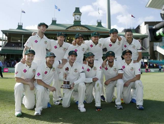 Australia's test cricket captain Steve Smith holds the Frank Worrell trophy among team mates after their third cricket test against the West Indies at the SCG in Sydney, January 7, 2016. REUTERS/Jason Reed/Files