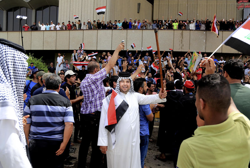 Supporters of Shiite cleric Muqtada al-Sadr chant slogans calling for governmental reforms as they wave national flags before ending their sit-in inside Baghdad's highly fortified Green Zone, Sunday, on May 1, 2016. Photo: Karim Kadim/AP