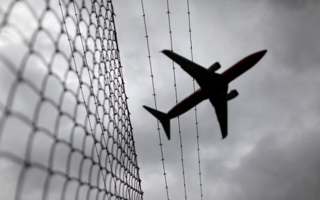 A passenger plane flies over a barbed wire fence as it approaches Sydney airport in this February 23, 2010 file photo. REUTERS/Tim Wimborne