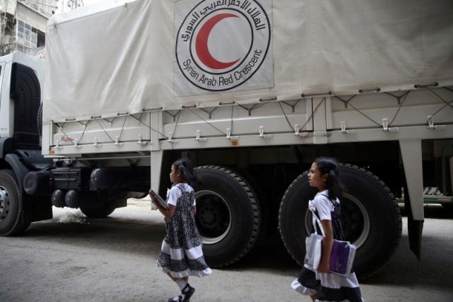 Twin girls walk near a Red Crescent aid convoy carrying urgent medical supplies in the rebel held besieged town of Douma, eastern Ghouta in Damascus, Syria May 26, 2016. REUTERS/Bassam Khabieh