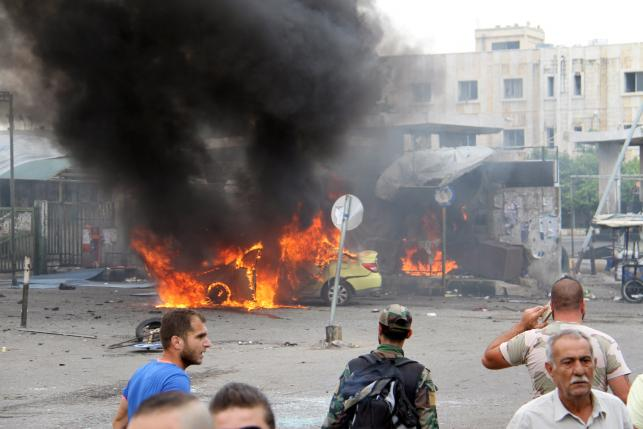 A Syrian army soldier and civilians inspect the damage after explosions hit the Syrian city of Tartous, in this handout picture provided by SANA on May 23, 2016. SANA/Handout via REUTERS