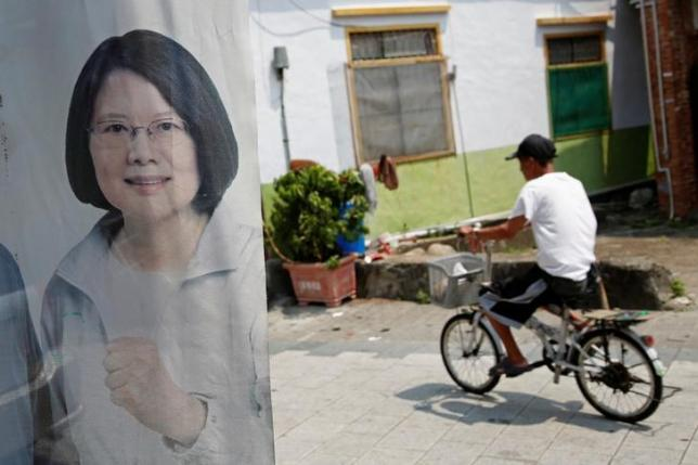 A man rides a bicycle past a flag with the image of Taiwan president-elect Tsai Ing-wen in Pingtung, Taiwan April 27, 2016. Picture taken April 27, 2016. REUTERS/Tyrone Siu