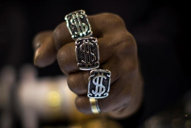 A man wears US dollar sign rings in a jewellery shop in Manhattan in New York City November 6, 2014. REUTERS/Mike Segar