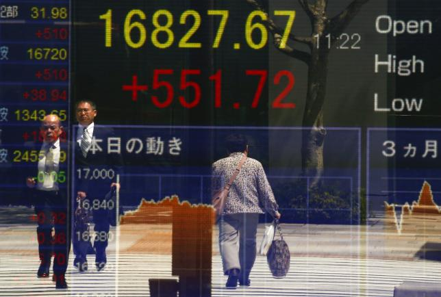 People are reflected in a screen displaying the Nikkei average outside a brokerage in Tokyo, Japan April 19, 2016. REUTERS/Thomas Peter