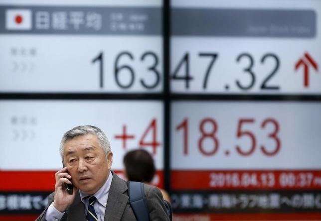 A man walks in front of an electronic board showing Japan's Nikkei average outside a brokerage in Tokyo, Japan, April 13, 2016.   REUTERS/Toru Hanai