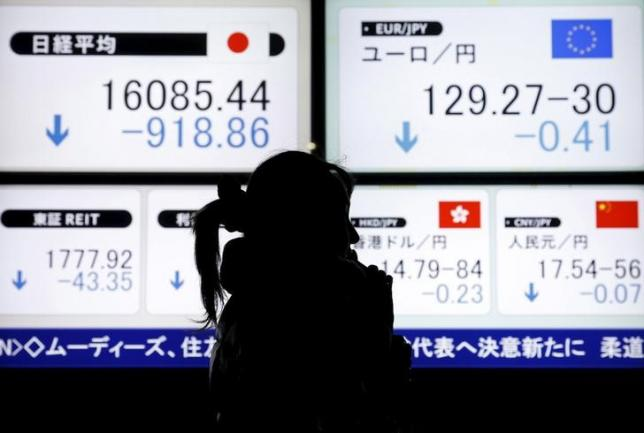 A pedestrian holding her mobile phone walks past electronic boards showing the Japan's Nikkei average (top L) and the Japanese yen's exchange rate against the euro (top R) outside a brokerage in Tokyo, Japan, February 9, 2016. REUTERS/Yuya Shino