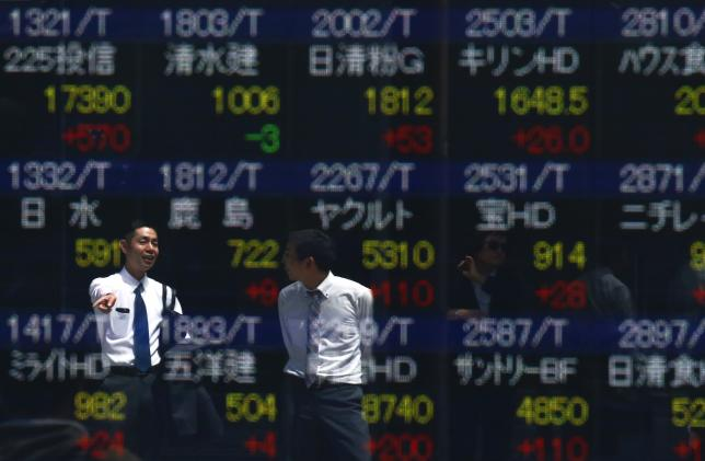 Men are refelcted in a screen displaying market indices outside a brokerage in Tokyo, Japan April 19, 2016. REUTERS/Thomas Peter