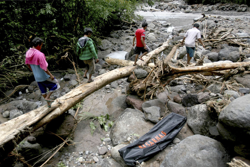 Locals walk near a plastic bag containing the body of a victim of floods in Sibolangit of North Sumatra, Indonesia,on Monday, May 16, 2016. Nearly two dozen students are reported missing in the rain-triggered floods and landslides at waterfall in western Indonesia. Photo: AP