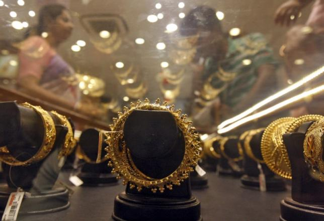 Gold bracelets are on display as a woman (L) makes choices at a jewellery showroom in Kolkata April 21, 2015. REUTERS/Rupak De Chowdhuri/Files