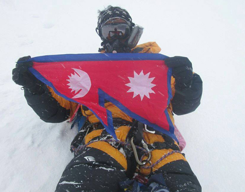 A Nepali mountaineer Anish Luintel holds the national flag after reaching the Mount Everest summit on May 21, 2016. Courtesy: Nepal Scouts