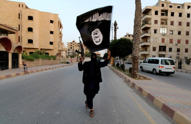 A member loyal to Islamic State waves a flag in Raqqa June 29, 2014. REUTERS/Stringer/File Photo