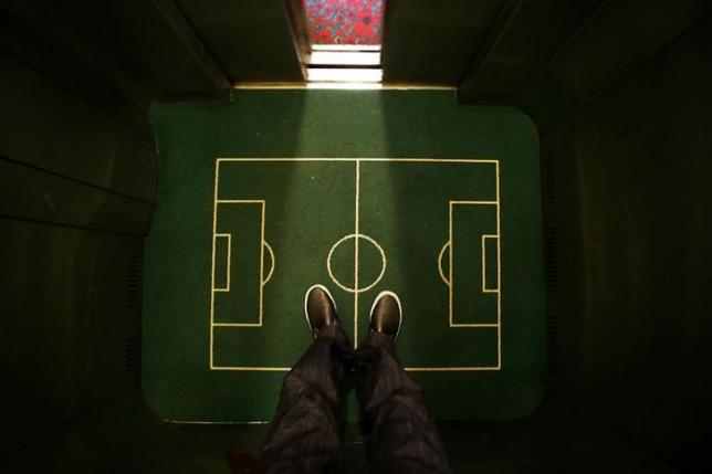 A  floor cover depicting a soccer pitch is seen in an elevator in a hotel in Curitiba city June 17, 2014. REUTERS/Ivan Alvarado/Files