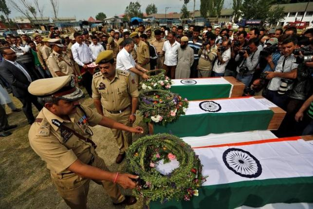Police officers lay wreaths on the coffins of three policemen who were shot dead at point-blank range in Srinagar, India May 23, 2016. REUTERS/Danish Ismail