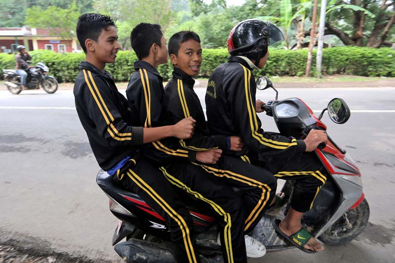 Four school children ride on a scooter in an unsafe way on their way home, in Kirtipur, on Saturday, May 21, 2016. Photo: RSS