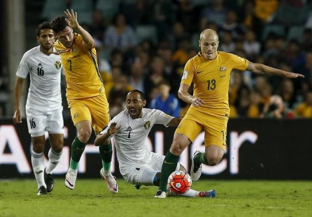 Football Soccer - Australia v Jordan - World Cup 2018 Qualifier - Sydney, Australia - 29/3/16 Jordan's Monther Abu Amara (C) is tackled by Australia's Mathew Leckie (L) and Aaron Mooy during their World Cup 2018 Qualifier at the Sydney Football Stadium. REUTERS/Jason Reed/Files
