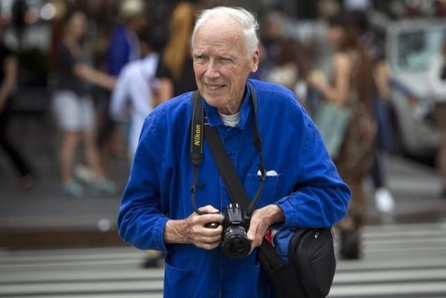 New York Times photographer Bill Cunningham crosses the street after taking photos during New York Fashion Week in the Manhattan borough of New York September 6, 2014.  REUTERS/Carlo Allegri/Files
