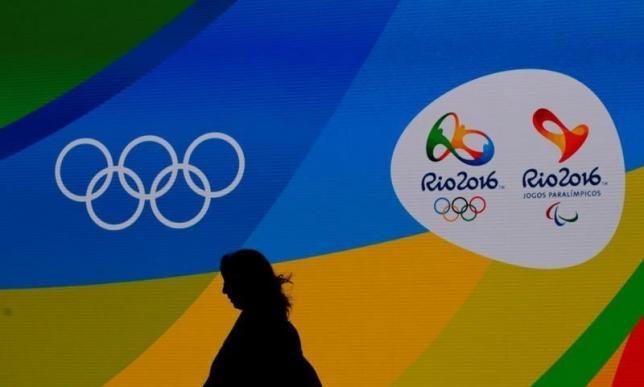 A journalist walks in front of a screen with olympics logos during the medal launching ceremony in Rio de Janeiro, Brazil, June 14, 2016. REUTERS/Sergio Moraes