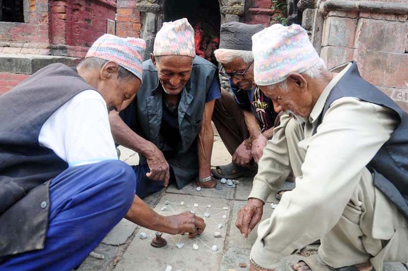 Elderly people playing baghchal, a kind of board game, during their leisure time in front of the Ganesh Temple in Khauma of Bhaktapur district , on Tuesday, June 21, 2016. Photo: RSS