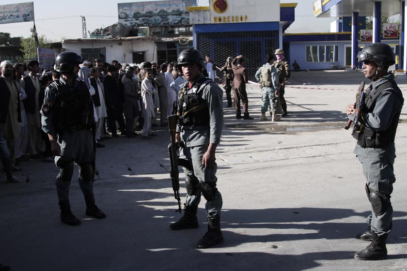 Afghan police soldiers inspect the blast site. AP