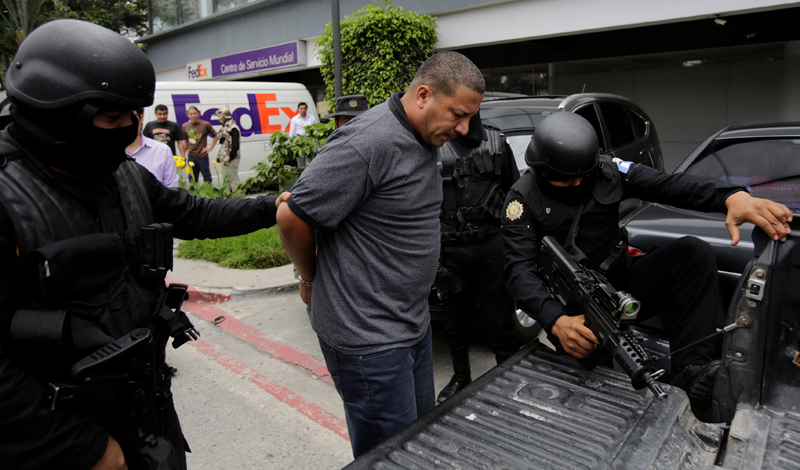 Police agents escort Luis Leonardo Mejia, suspected leader of a human trafficking ring that smuggled illegal immigrants from Pakistan, Afghanistan, India and Nepal, according to local media, outside the hotel where he was detained in Guatemala City, Guatemala, June 28, 2016. REUTERS