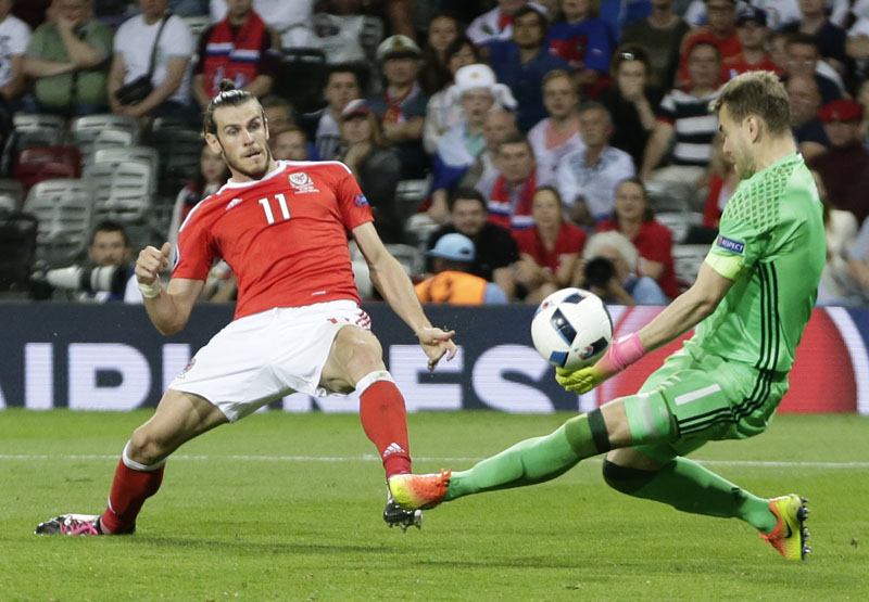 Wales' Gareth Bale (left) scores his side's third goal  past Russia goalkeeper Igor Akinfeev during the Euro 2016 Group B soccer match between Russia and Wales at the Stadium municipal in Toulouse, France, on Monday, June 20, 2016. Photo: AP