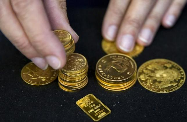 A worker places gold coins on display at Hatton Garden Metals precious metal dealers in London, Britain July 21, 2015. REUTERS/Neil Hall/Files