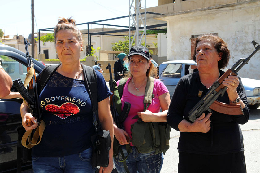 Women pose with guns in front of journalists in the Christian village of Qaa, where suicide bomb attacks took place on Monday, in the Bekaa valley, Lebanon June 28, 2016. Photo: Reuters/File