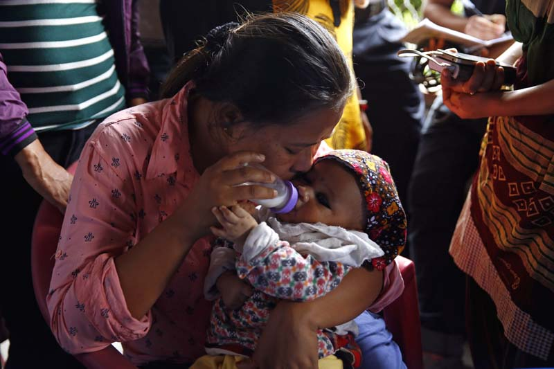 A mother, relative of one of the 12 deceased Nepalis in Kabul suicide attack, feeds her child while waiting for the body, at the Tribhuvan International Airport, on Wednesday, June 22, 2016. Photo: Skanda Gautam
